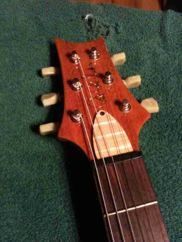 Custom cut flame maple truss rod cover on a PRS guitar